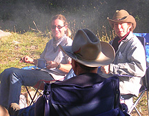 Amy Finger (left) and Nancy Hedberg enjoy cowboy coffee by the campfire at camp on Sand Creek a year ago.