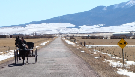 An Amish buggy driver traveling on Colfax Lane south of Westcliffe. Road crews have recently put up signs to warn motorists of the slower moving vehicles on area roads.